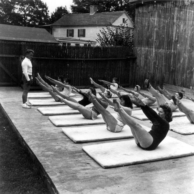 Joseph Pilates teaching a group of dancers the teaser in an outdoor mat class